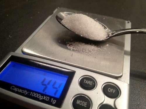 Ein Teelöffel Zucker auf einer Präzisionswaage