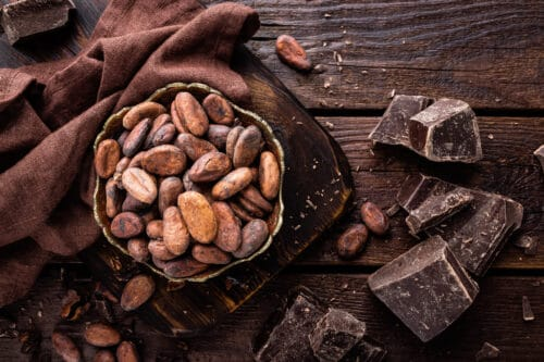 Cocoa beans and chocolate on wooden background By sea_wave licenced via envatoelements